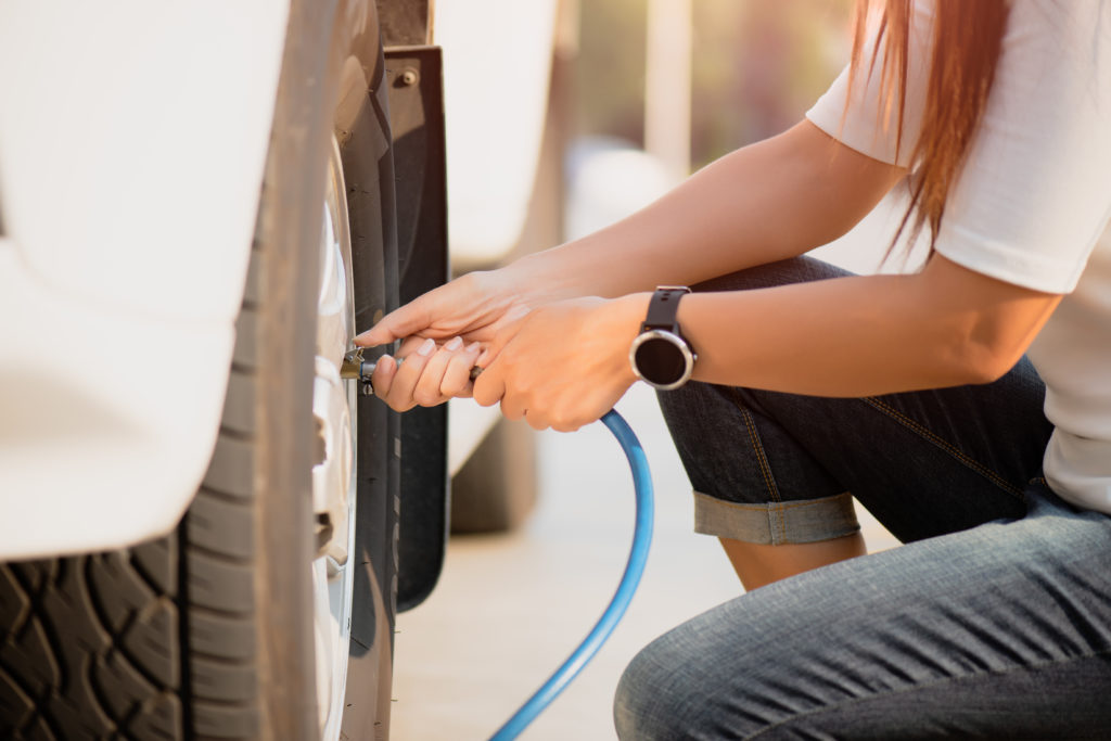 Woman driver checking air pressure and filling air in the tires close up.